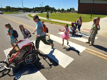 Melinda Thayer and Ashley Ovsijenko walk with their children to Irwin Intermediate School on Fort Bragg. Thayer says she can often get to school and back home faster than parents who drive.