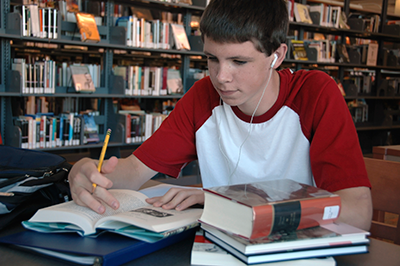 HS boy working in library