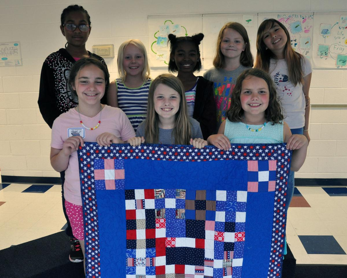 Dahlgren School students display a lap quilt they created to donate to a wounded warrior.