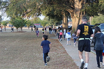 Dexter PIE Partners and students pass the front of the school during the Turkey Trot Fun Run.