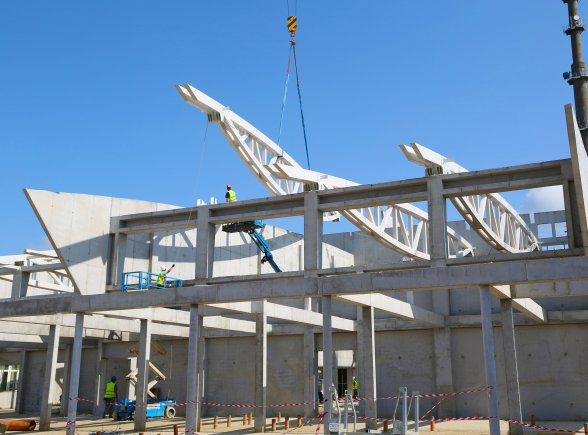 In July, construction workers install massive prefabricated support trusses atop the gymnasium that sits between the DODDS-Europe elementary and middle schools at Supreme Headquarters Allied Powers Europe in Mons, Belgium. The wooden beams serve as both structural and aesthetic elements.