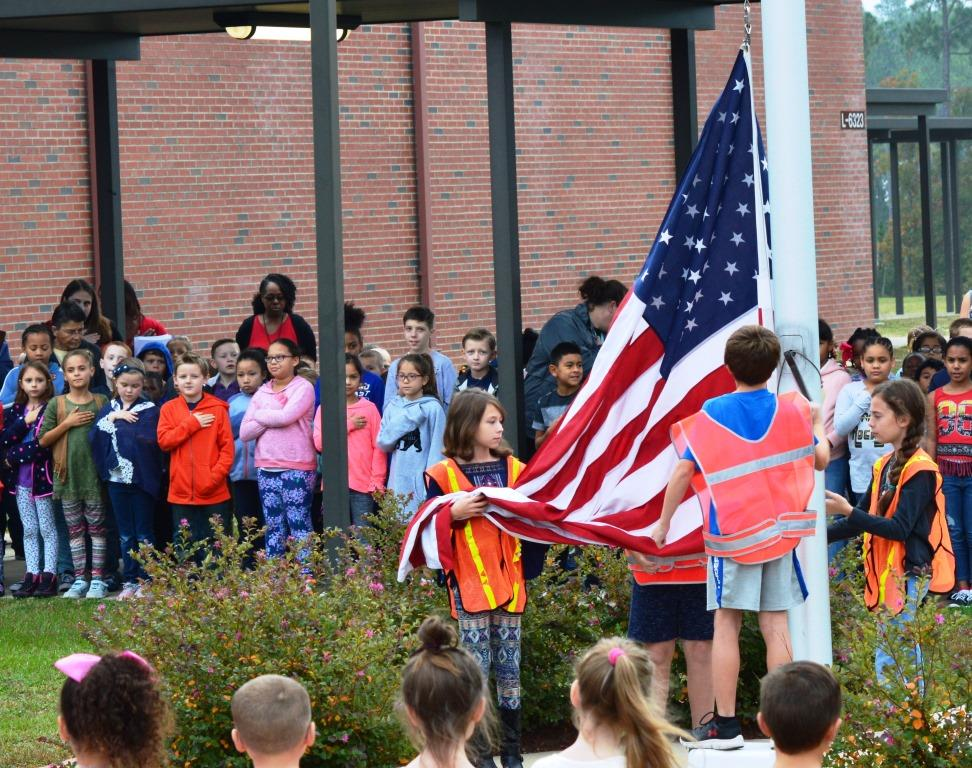 The Gordon Elementary School flag team raises the flag during the Veterans Day ceremony
