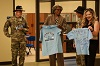 Priscilla Joiner (center) principal of Kimberly Hampton Primary School accepts two school shirts flown and signed by the aircrews of the OH-58D Kiowa Warrior farewell final flight in April. Lt. Col. Adam Frederick and Command Sgt. Maj. Timothy Overbey, command team of 1st Squadron, 17th Regiment, 82nd Combat Aviation Brigade, presented the shirts with a certificate of authenticity.