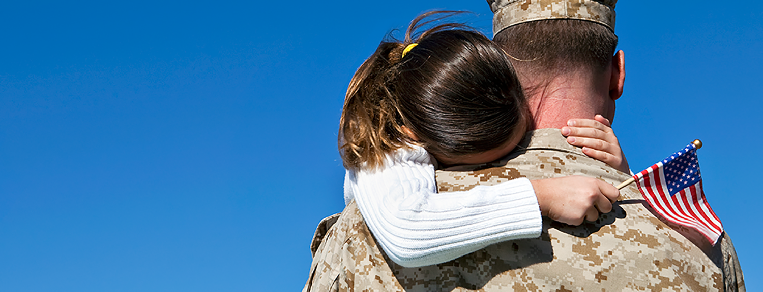 Military Dad hugging daughter with American Flag in her hand