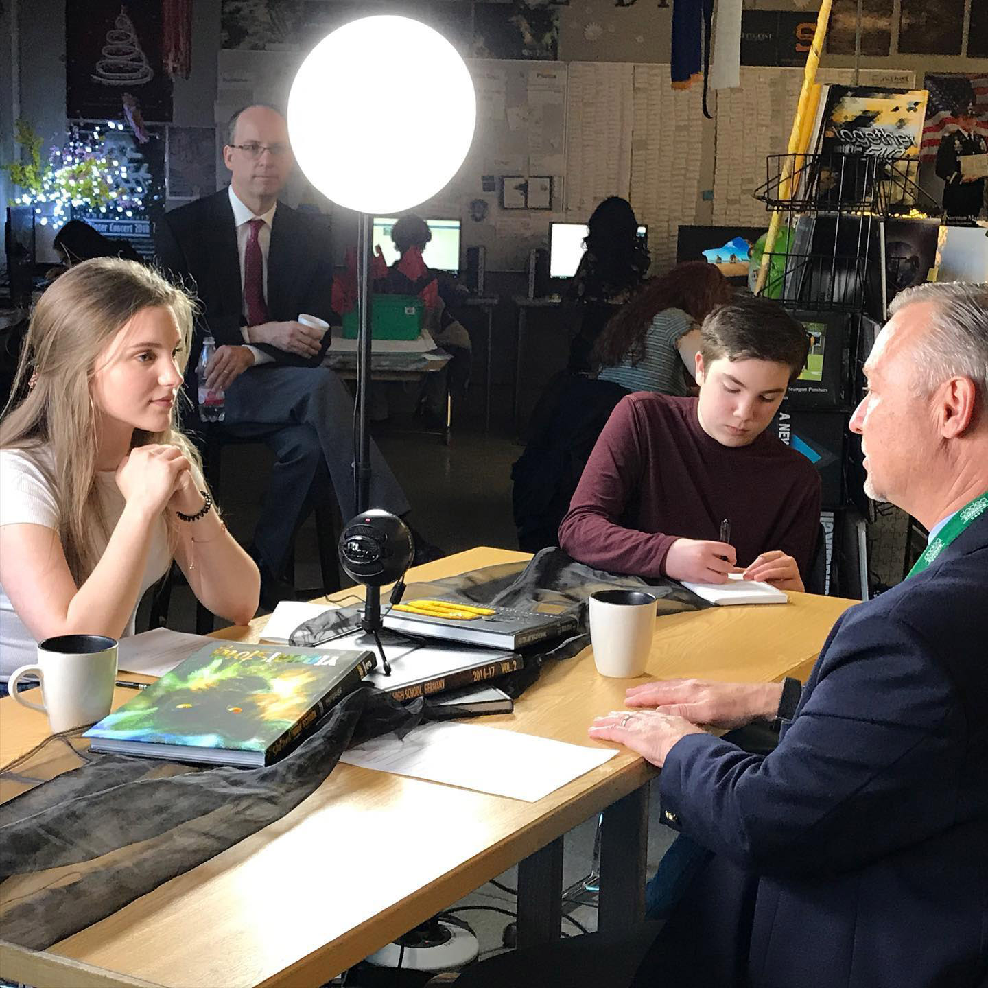 DoDEA Europe East Superintendent Steve Sanchez being interviewed by Stuttgart HS student journalist Scarlet Meads '20, assisted by George Svoboda '22  with SHS Principal Rick Renninger looking on.