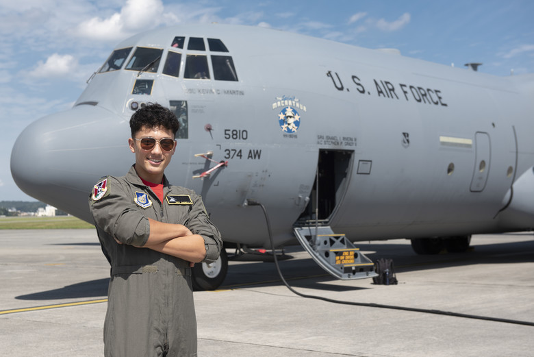 Joey DeGrella, Yokota High School senior and Junior Reserve Officer Training Corps. class commander, poses for a photo in front of a C-130J Super Hercules.