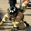 Jim Ussery, Fort Rucker firefighter, teaches the students at Fort Rucker Primary School to not be afraid of firefighters in their firefighting uniforms during an event for Fire Prevention Week at the Fort Rucker Primary School Oct. 12.