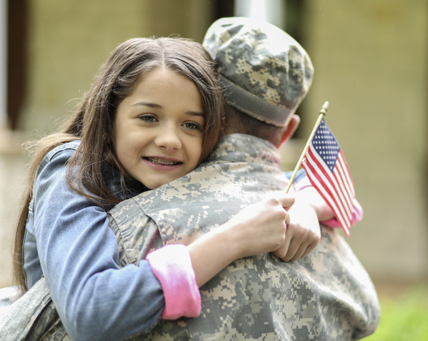 Girl hugs soldier dad