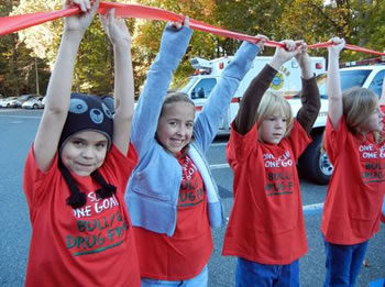 Josephine, Ana, Reagen and Jaime are among 137 Burrows Elementary School fourth-and fifth-graders gathered outside the school, holding a red ribbon to collectively pledge against substance abuse. The event, held Monday, kicked-off the schools' Red Ribbon Week.