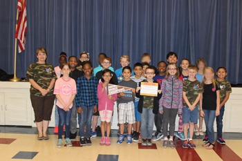 Ms. M's class poses with the award certificate and banner from the Leukemia & Lymphoma society.